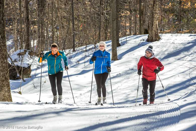 three cross country skiers going up a groomed trail