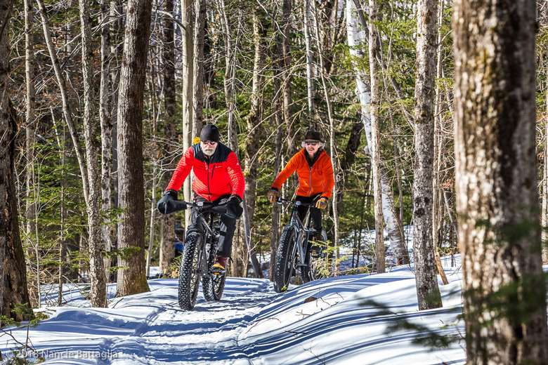 two people riding fat tire bikes on a trail in winter