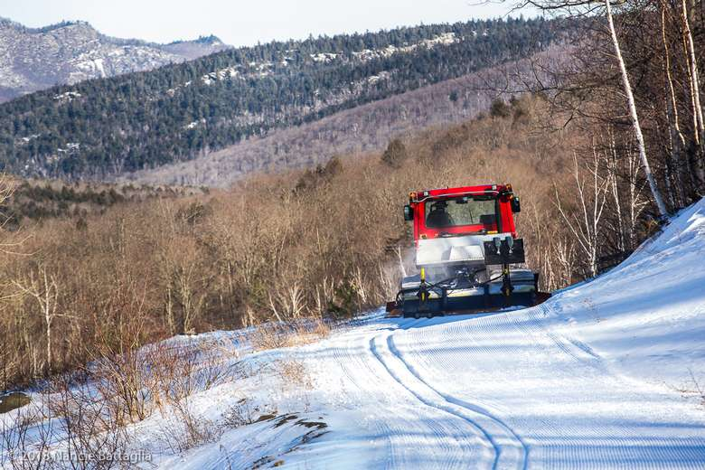 red vehicle grooming a snowy trail in winter