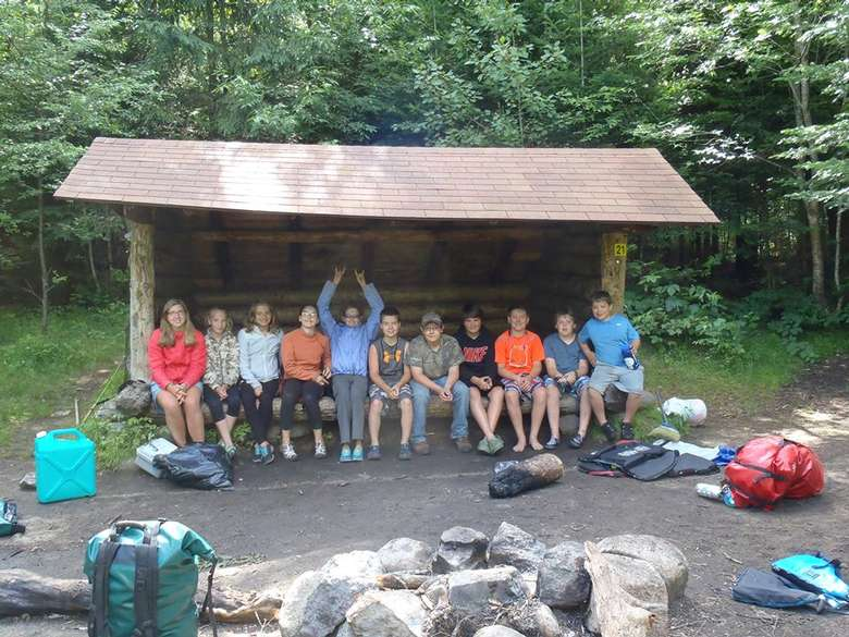 group of hiker kids sitting in a lean to