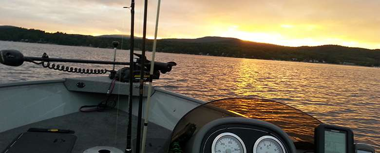 three fishing rods in the bow of a boat at sunset