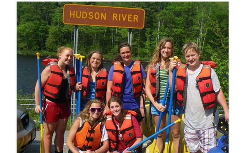 a group of rafters wearing red life vests while standing in front of a hudson river sign