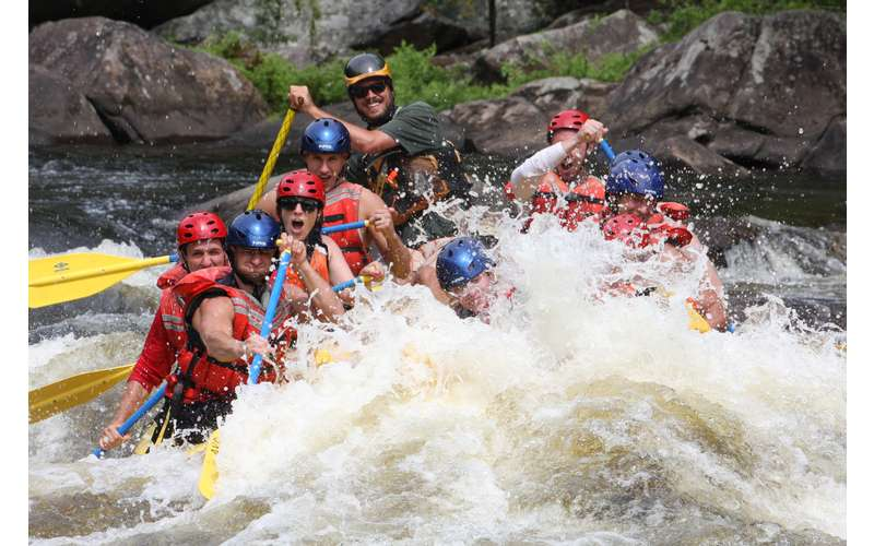 rapids splashing a yellow raft full of whitewater rafters