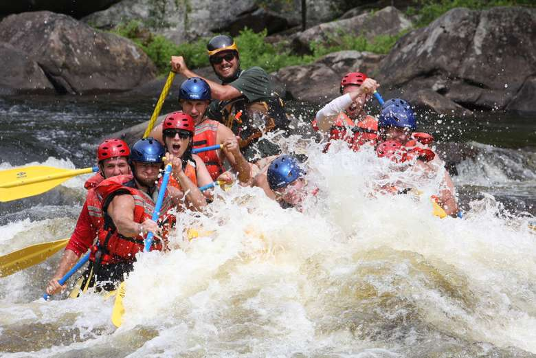 rapids splashing a yellow raft full of whitewater rafters