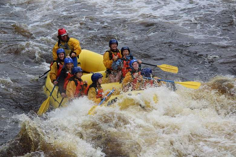 whitewater rapids splashing a group in a yellow raft