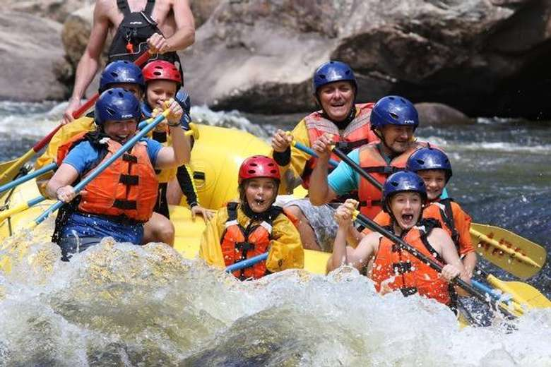 whitewater raft full of paddlers going through a rapid