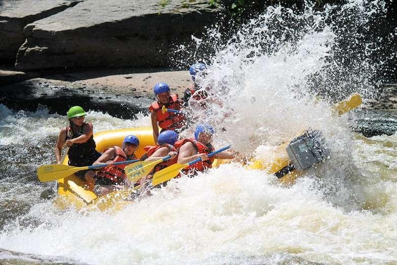 whitewater raft crashing through a rapid