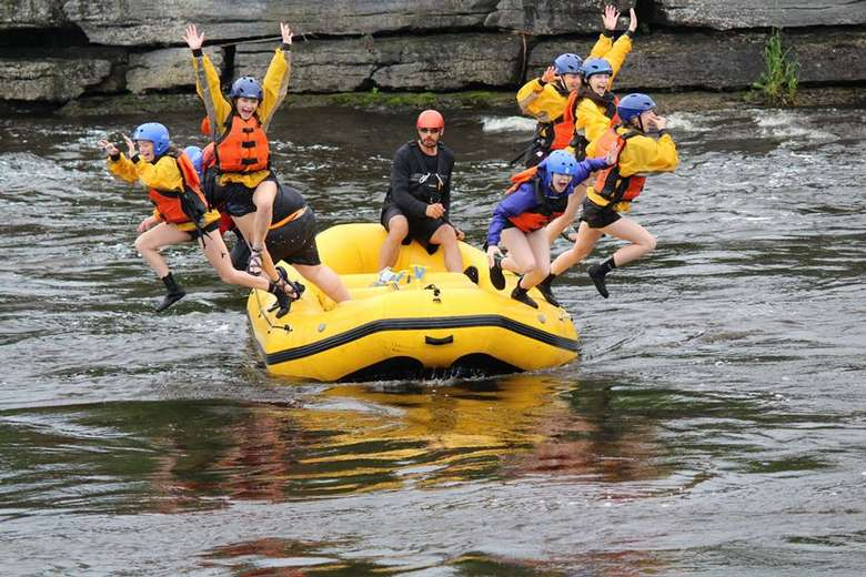 group of rafters in life jackets and helmets jumping out of their raft into the river