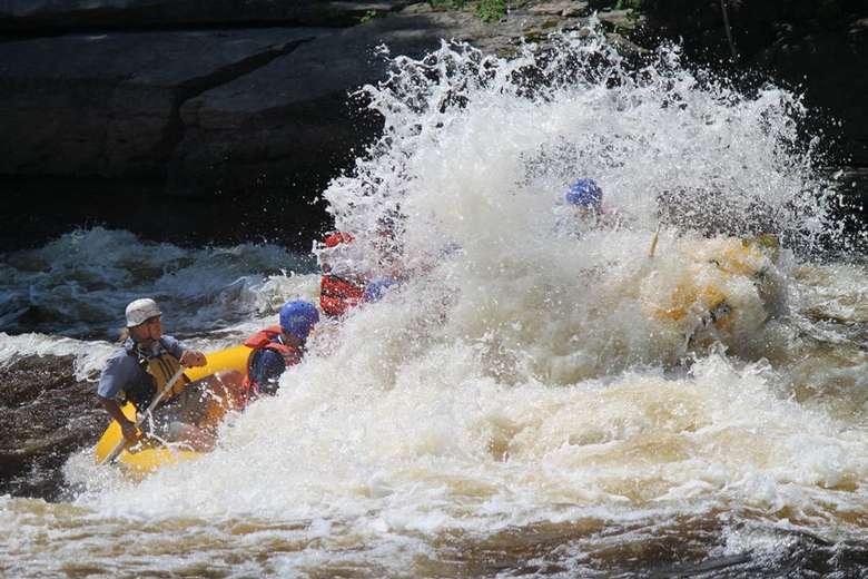 whitewater raft crashing through the rapids