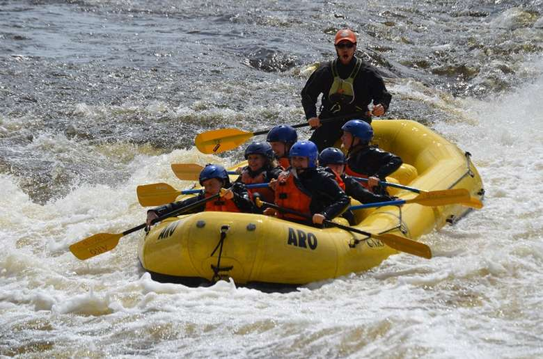 yellow whitewater raft cruising through a calm section of river