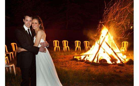 bride and groom hugging with a large bonfire in the background