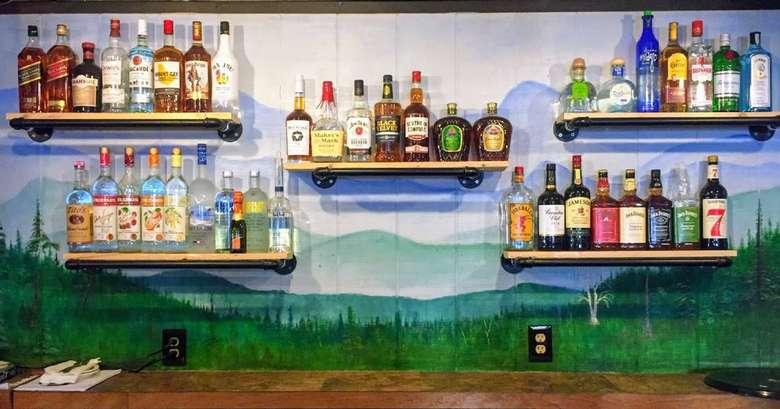 bottles of liquor on shelves on a wall