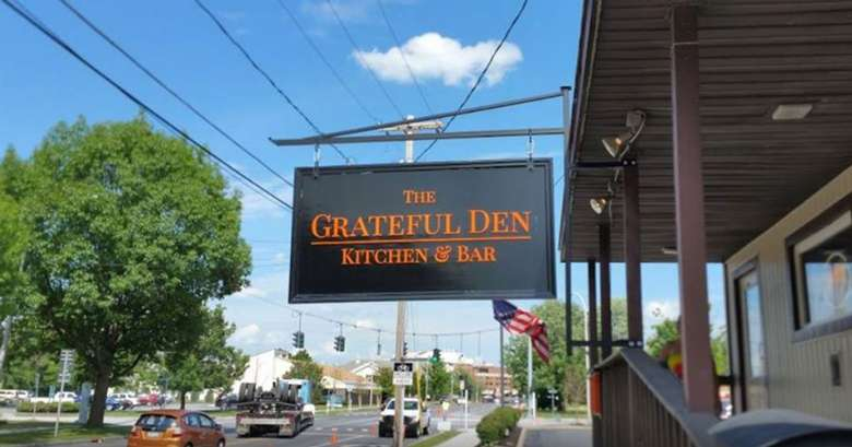 the grateful den kitchen and bar sign outside the building
