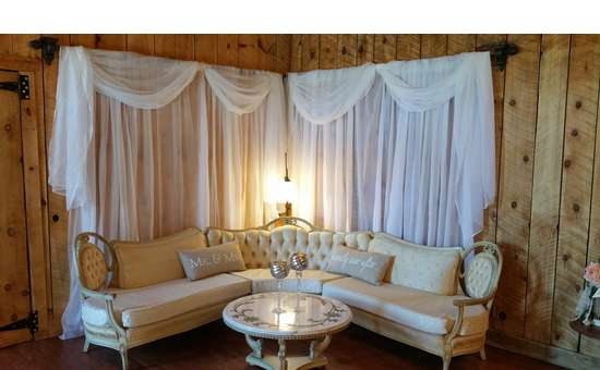 white couch and curtains draped around the sides