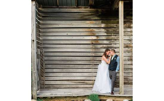 couple gazing into each other's eyes in front of barn