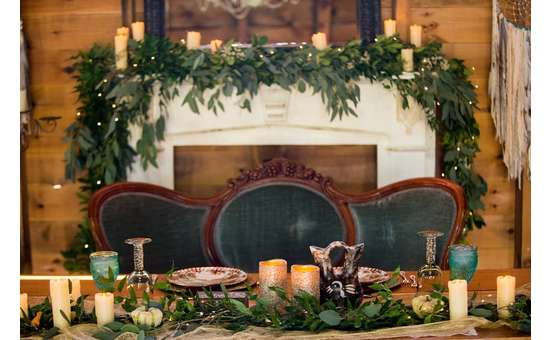mantel decorated with greenery and candles, with a table and sofa