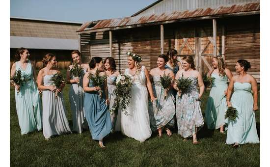 smiling bridal party in front of a barn