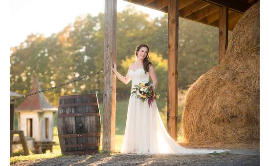 bride standing beside a barrel and hay.