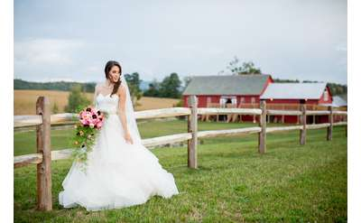 bride standing in front of barn and wooden gate