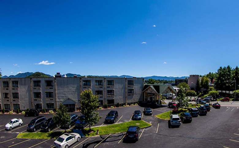 exterior view of hotel rooms and parking area with mountains in distance