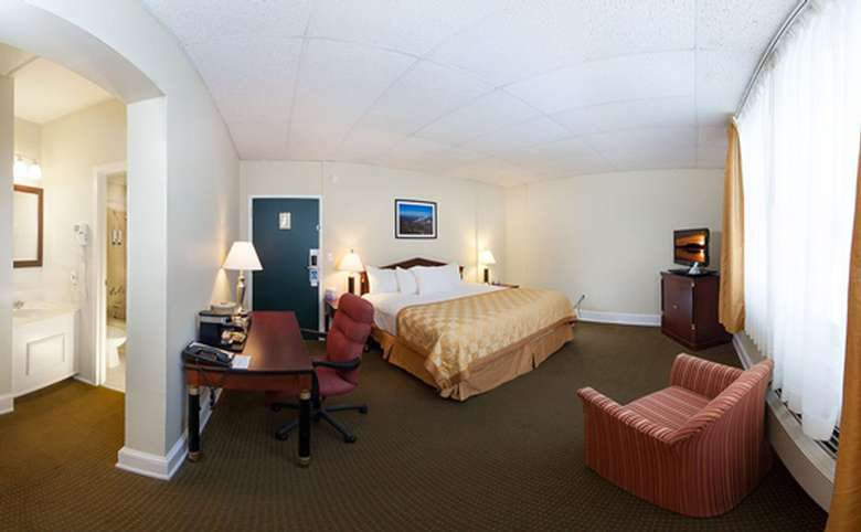 interior view of hotel room with large bed, desk, tv and sitting area