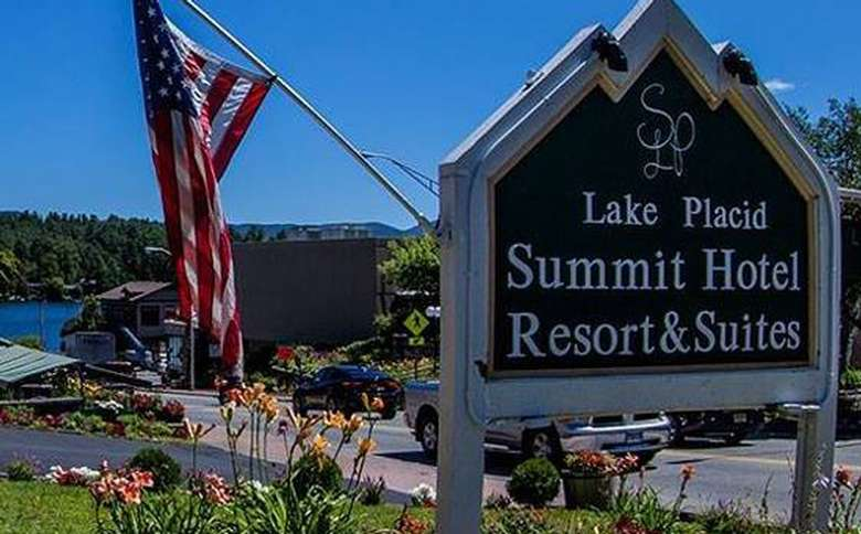 view of lake placid summit hotel resort and suites sign with flag