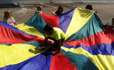 Kids playing with parachute with one boy on it