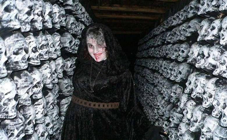 scary woman standing in hallway of skulls