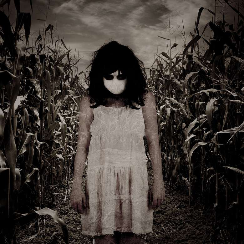 woman in dress and mask standing in creepy corn maze