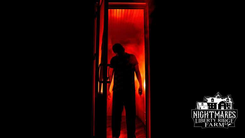 person standing in doorway in the darkness with red light behind them