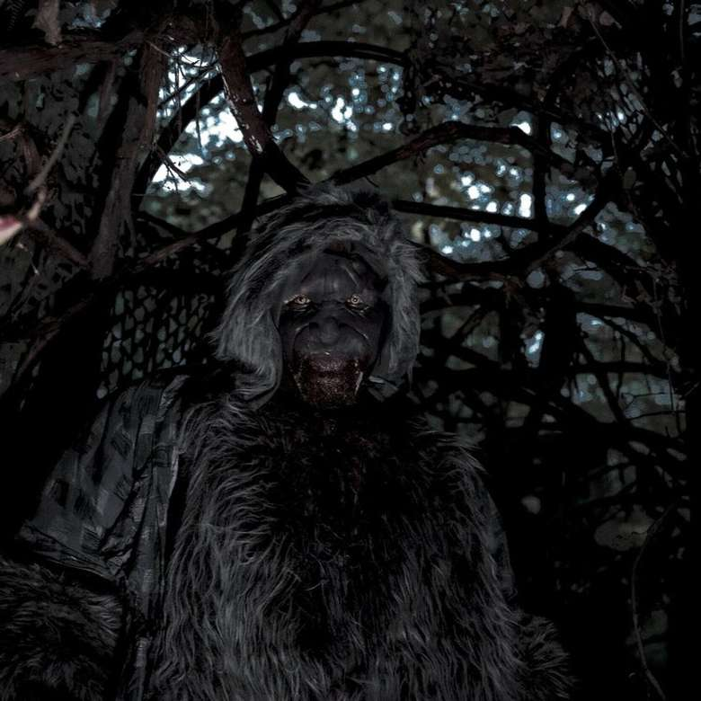 man dressed in scary costume in a forested area