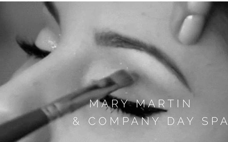 a makeup brush on an eye with the text Mary Martin & Company Day Spa