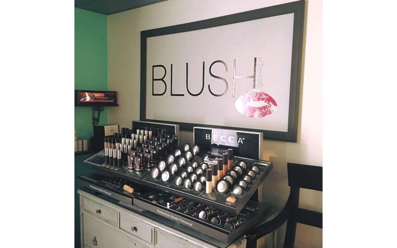 makeup products displayed under a sign that says Blush
