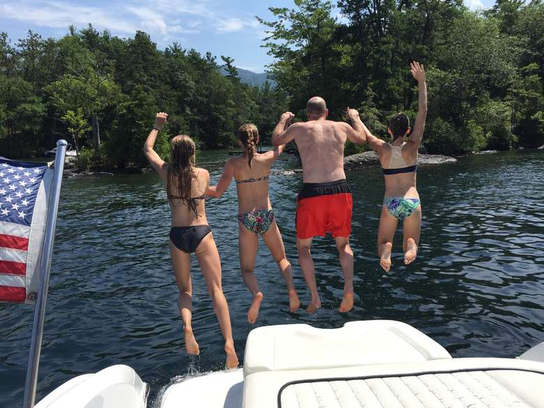 four people holding hands and jumping off a boat into the water