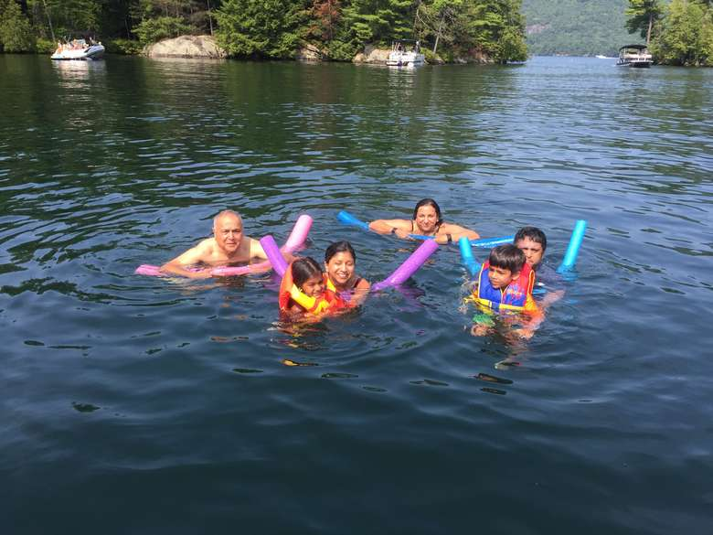 six people swimming with noodles in lake george