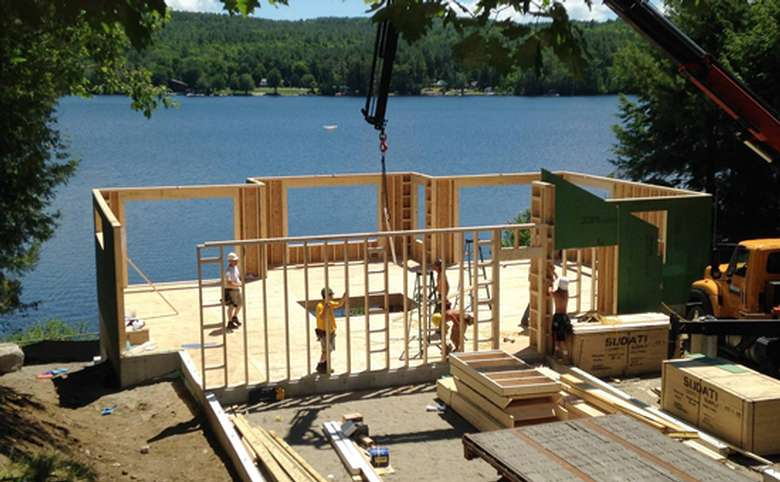 the wooden frame of a home being built on the waterfront