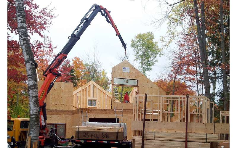 a large red crane helping to construct the frame of a house in autumn