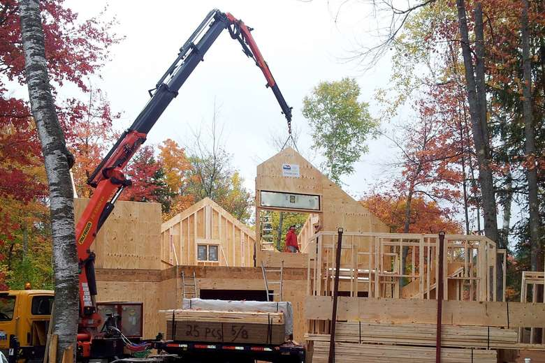 a large crane helping to put a house frame together during autumn