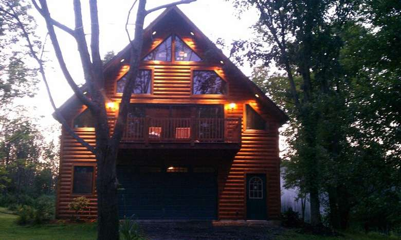 a multi story rustic house with lights on the exterior near the balcony