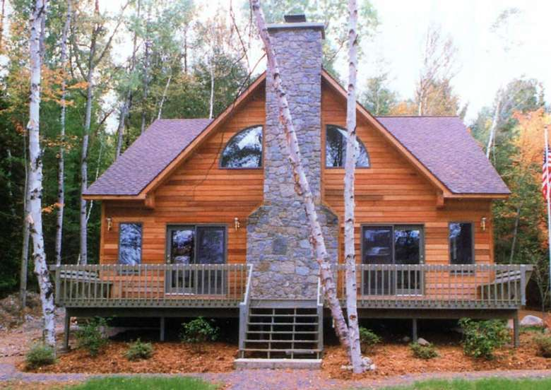 a rustic home in the woods with a large stone chimney in front by the deck