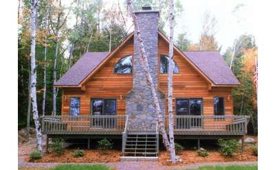 a brown wooden home with a stone chimney and front porch