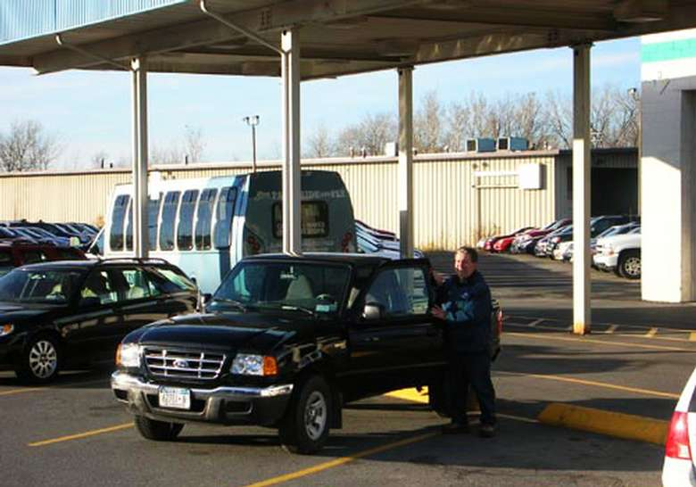 man entering a black pick-up truck with park ride and fly shuttle in the background