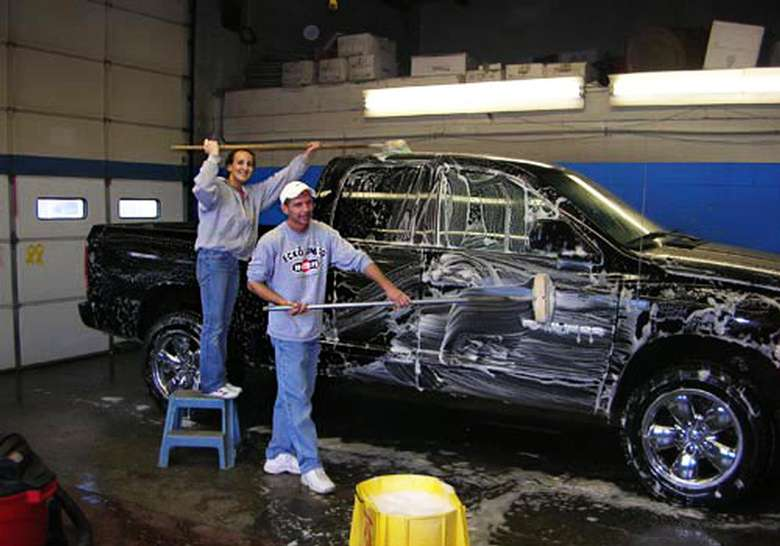 park, ride and fly employees washing a black pick-up truck