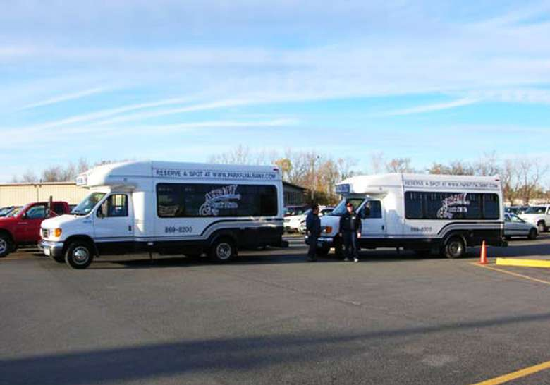 two park, ride and fly shuttles parked next to each other