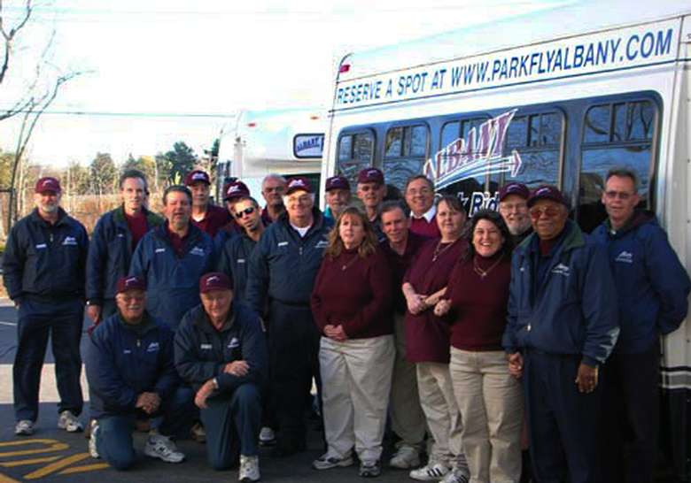large group of smiling albany park, ride and fly employees standing in front of shuttle bus