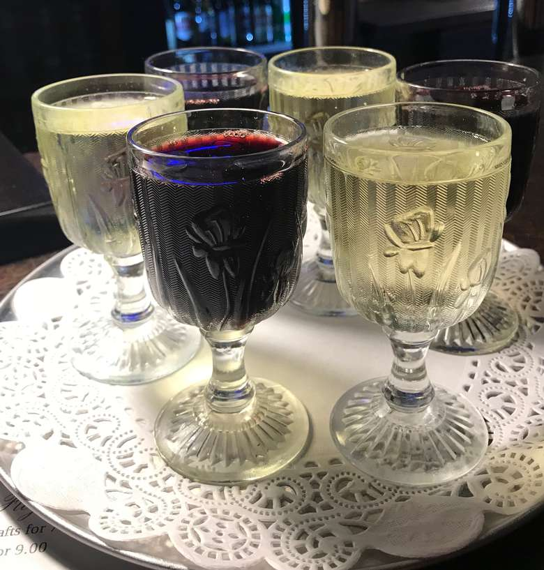 flight of red and white wines on a tray with a doily