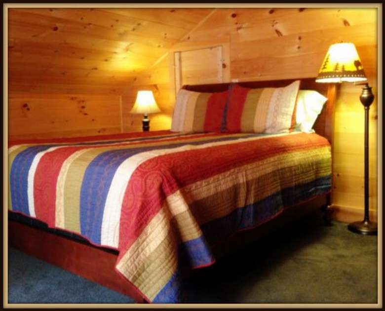 queen sized bed with a striped comforter in a room with wooden walls
