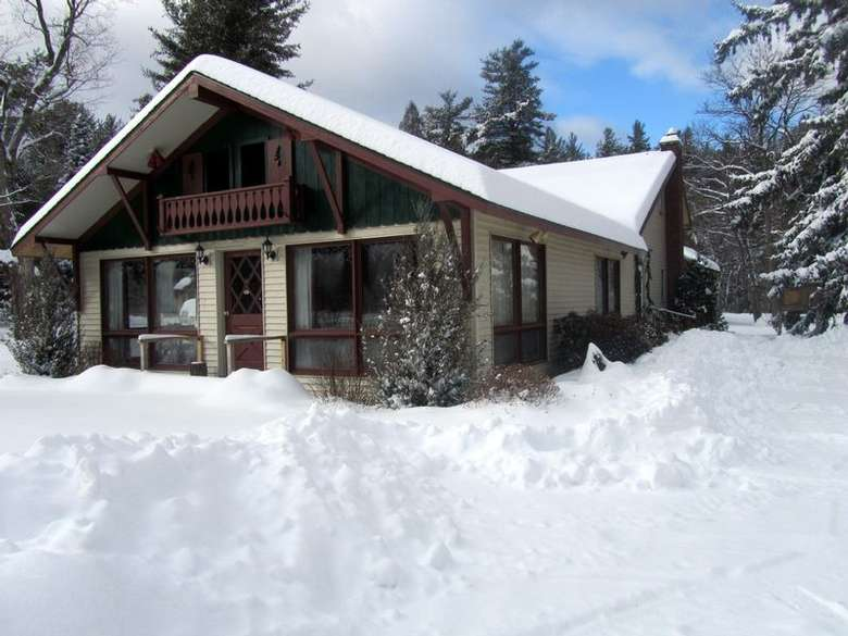 exterior of a house in the woods after a snowstorm