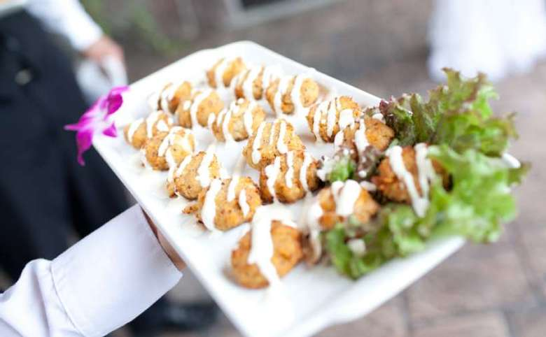 A large platter of hors d'oeuvres being held by waitstaff.