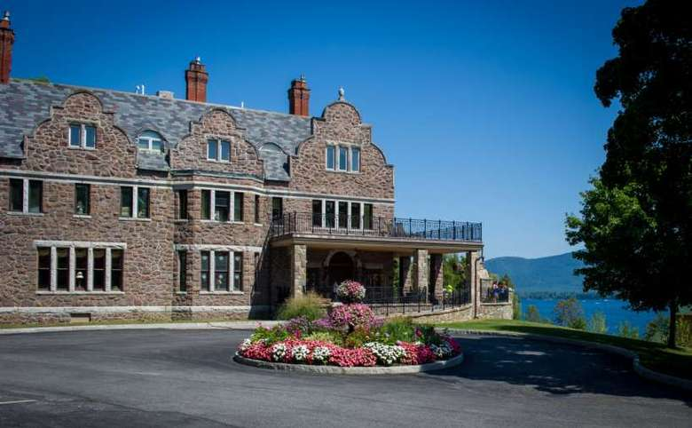 The outside of The Inn at Erlowest, a large stone inn with many windows and fireplaces, as seen from the entrance. The lake and mountains are seen in the distance.